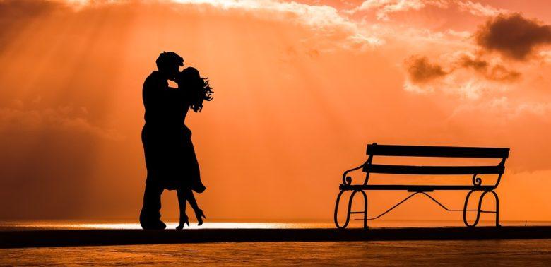 (夕日を背景にしたカップルの写真です)